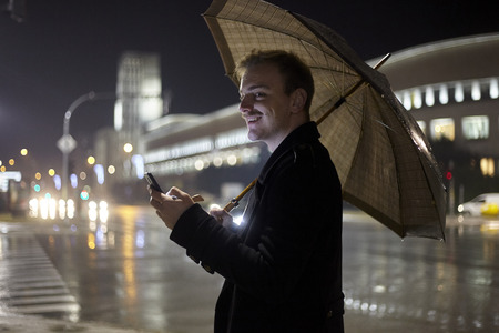 one young man smiling, 20-29 years old, walking outside while holding an umbrella because its raining, an typing on his smartphone.