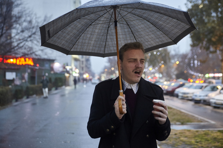 one young businessman, 20-29 years old, yawning while holding an umbrella and a cup, while going to a work.