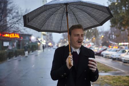 un jeune homme d'affaires, 20-29 ans, bâillant en tenant un parapluie et une tasse, en allant à un travail.