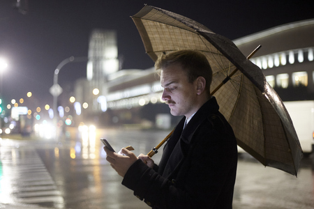 one young man, 20-29 years old, walking outside while holding an umbrella because its raining, an typing on his smartphone. Stok Fotoğraf