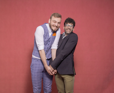 men acting silly, making a face, hugging together. photo-shoot in studio.