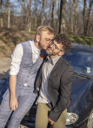 two man, gay couple kissing on cheek. outdoors, while sitting on car hood.
