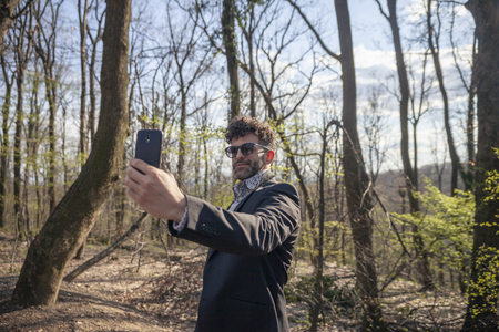 one young handsome man, talking a selfie outdoors in nature. Serious face expression, wearing sunglasses.