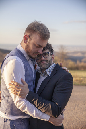 gay couple in love, intimate & hugging together, outdoors in nature.