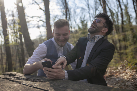two men, using smartphone in forest. Selective focus on foreground (smartphone), two men out of focus (pointing fingers).