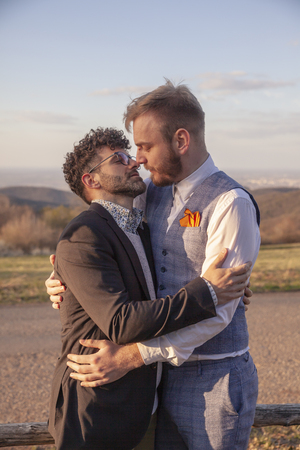 two men, gay couple hugging each other about to kiss, face to face. intimate and standing close by, outdoors. Banco de Imagens