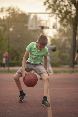 One boy, exercising dribbling ball between his legs. Outdoors on a basketball court. Looking to camera Reklamní fotografie