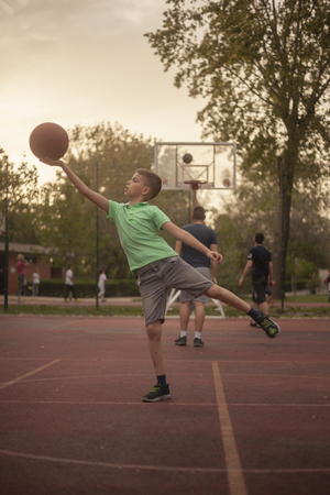 one nine year old boy, holding basketball ball in his hand like, like worshiping it. outdoors on a basketball court, with people behind.