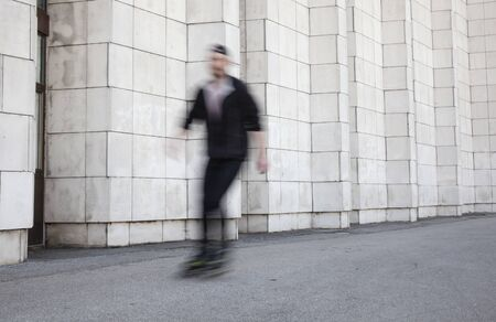 one man, riding inline skates, blurry because of moving motion. in background is wall.
