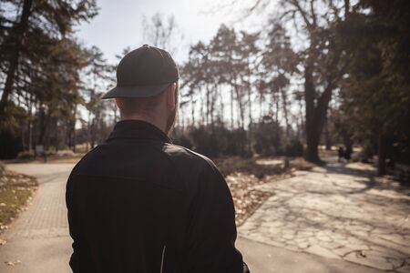 one young man, wearing cap backwards, looking to park. shot from back, rear view. Stock Photo