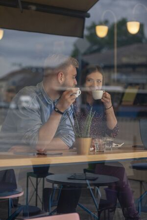 two friends sitting together in a cafe, drinking coffee. shot thought window with reflections. 版權商用圖片
