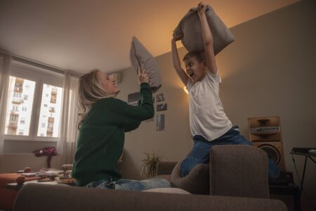 young woman and boy, pillow fight at home, having fun in their living room.