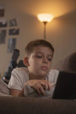 one boy, using a tablet, in bed at home.