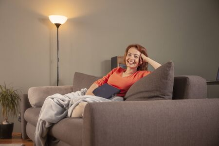 one woman, sitting in sofa, relaxing at her home with a book in her hands, wrapped in blanket. looking at camera.