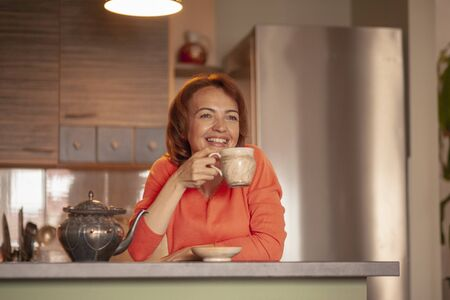 One blissful beautiful woman, 40 years old, drinking tea, relaxing in her home kitchen.