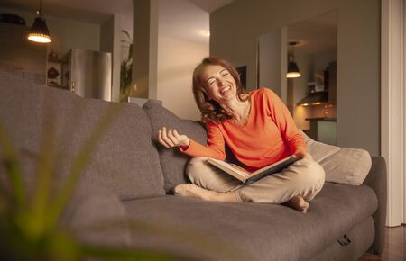 one woman laughing, while relaxing in her sofa, at home. looking at camera.