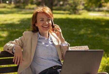 one mature joyful woman listening over phone, in a park. Standard-Bild