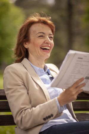 woman laughing while reading a book.