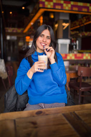 Portrait of pretty brunette in a cafe. Enjoying latte and looking at camera.