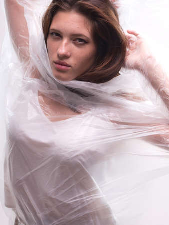 conceptual portrait, one young beautiful woman wraped in plastic sheet. Shot in studio, white background. Imagens