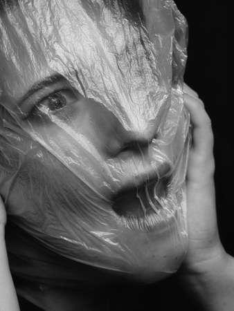 high key. Conceptual portrait with plastic sheets. One young woman strugling with plastic sheets.