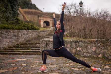 one young woman, stretching outdoors, on a winter day.