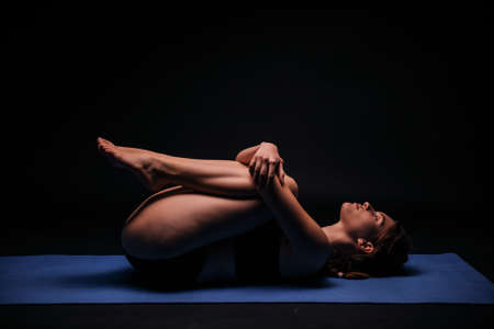 one young woman, exercising yoga, laying on a mat; calmly resting and streching in fetus position. shot on black background. Standard-Bild