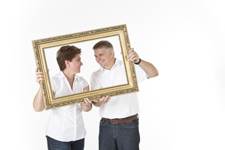 Middle-aged couple looking at each other in picture frame photo