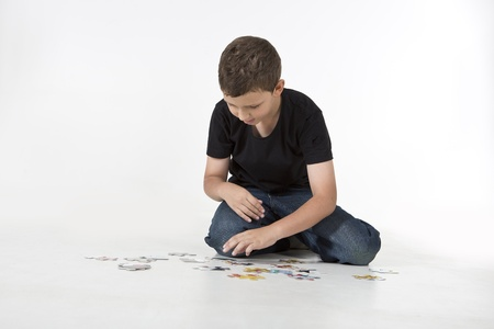 A young boy is working on a puzzle photo