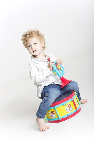 Happy boy playing with musical instrument toys photo