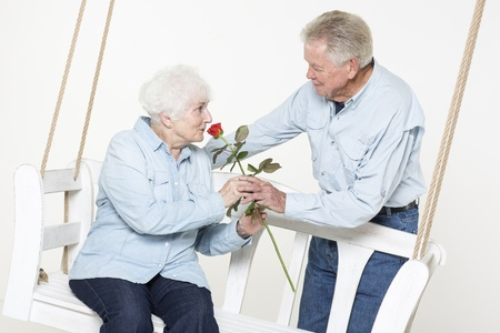 70 75 years: Senior man presents his wife with a flower