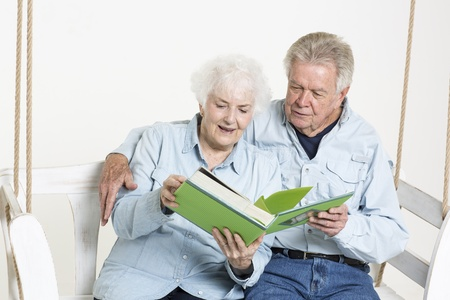 Senior couple looks at picture album Stock Photo - 22115998