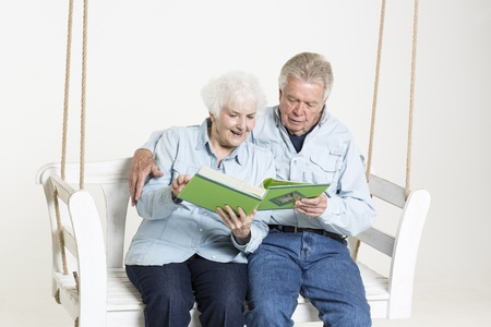 Senior couple looks at picture album Stock Photo - 22142453