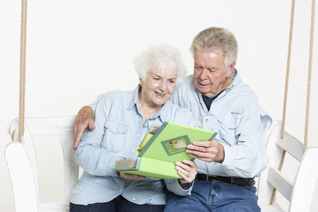 Senior couple looks at picture album photo