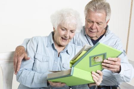 Senior couple looks at picture album Stock Photo - 22142456