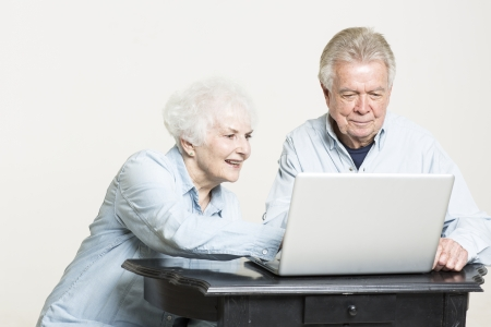 Senior couple looks at computer screen photo