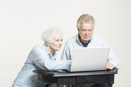 Senior couple looks at computer screen concerned photo