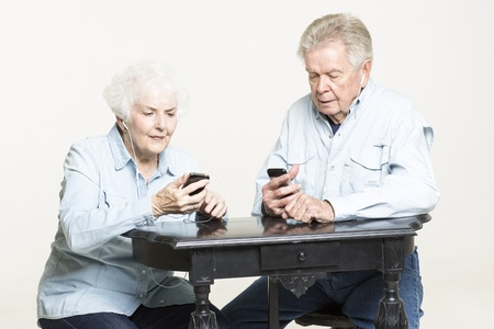Senior couple is listening to music in earphones photo