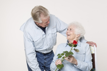 Senior man presents woman with a flower photo