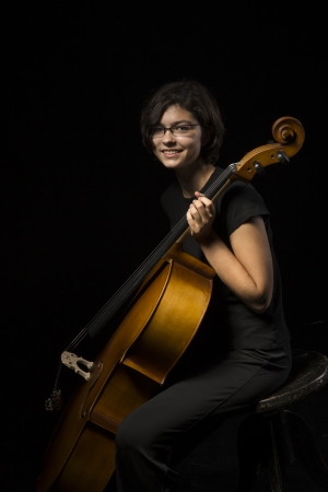 Young cellist holds instrument