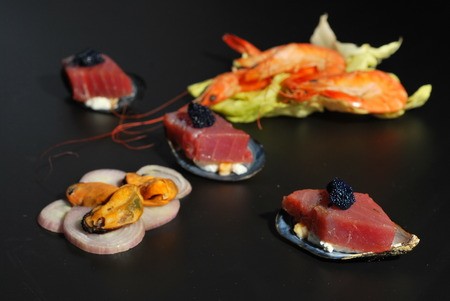 Marinated tuna with mussels and shrimp on a bed of salad and shallot photo