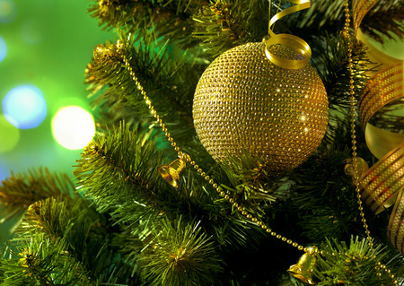 Golden ball on the Christmas tree branch on a blurred  green background photo