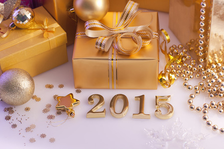 Christmas decorations, gifts and numbers in golden color on a purple background photo