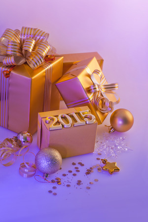 new year eve beads: Christmas decorations, gifts and numbers in golden color on a purple background