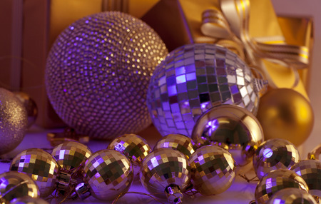 new year eve beads: Christmas decorations and gifts  in golden color on a purple background