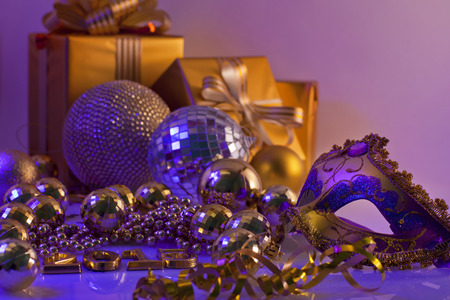 Christmas decorations and gifts  in golden color on a purple background photo