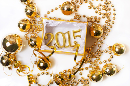 new year eve beads: Christmas decorations and figures gold color on a white background Stock Photo