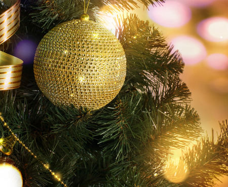 Golden ball on the Christmas tree branch on a blurred orange background photo