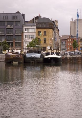 In Antwerp Harbor, three barges are moored opposite a waterfront cafe.