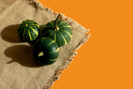 Three small green pumpkins lie on a napkin, light orange background, free space for an inscription
